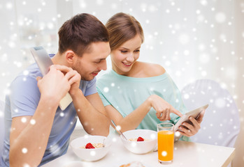 smiling couple with tablet pc having breakfast