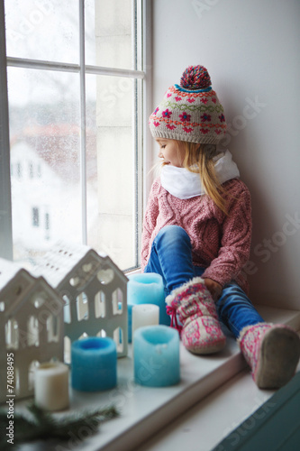Sitting on a window sill and looks at the street - 74088495