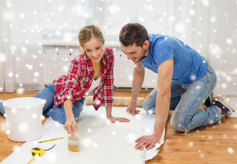 smiling couple smearing wallpaper with glue
