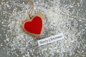 Merry Christmas card with red canvas heart on snowy surface