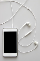White smart phone with earphones and isolated screen on table