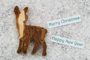 Merry Christmas and Happy New Year card with wooden roe deer