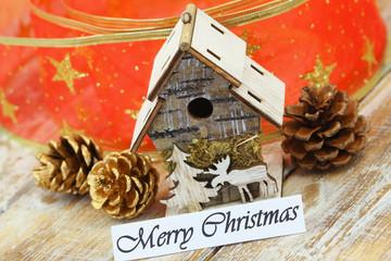 Merry Christmas card with miniature bird feeder, pine cones