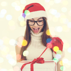 Excited Christmas woman unwrapping gift box. Bokeh light effect