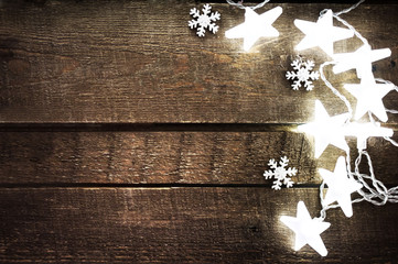 Christmas rustic background with lights, snowflakes, stars and f