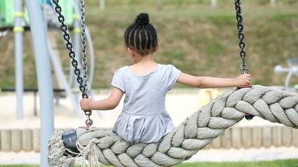 Young girl sits alone on a swing as children play around her