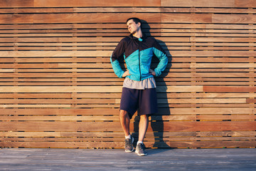 sportsman standing and resting near the wooden wall