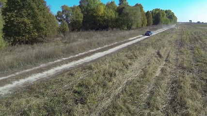 green car goes on  dirt road in  field. Aerial view