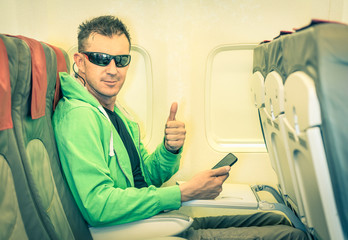 Hipster man passenger satisfied with thumbs up in airplane