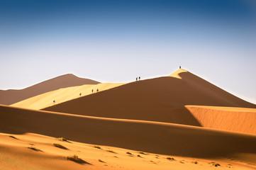 Tourist people hiking on sand dune at Deadvlei near Sossusvlei