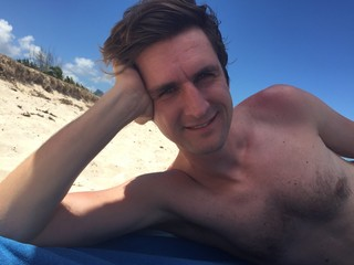 man laying at beach under umbrella
