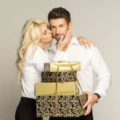Blond woman kissing handsome man with gifts