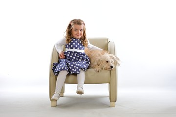 Litle girl and her dog on the beige leather seat