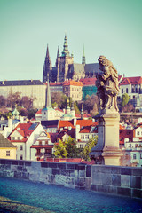 Statue on Charles Brigde against St. Vitus Cathedral in Prague