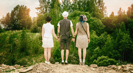 young active guy and girls hipsters hold hands over an abyss
