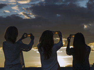 Three woman taking a picture at sunset with mobile phone