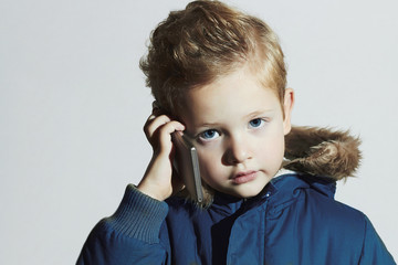 little boy with cellphone.child in winter coat.fashion kids