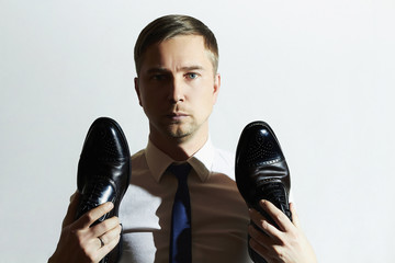handsome man holds shoes.Businessman in tie.Fashion boy