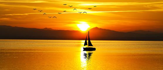 puesta de sol panoramica en el mar con un velero