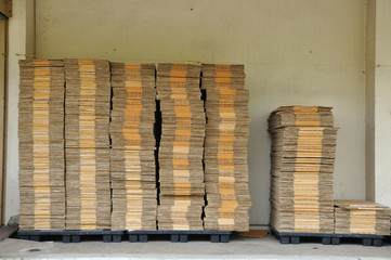 Many unpack paper box stacking on black pallet in front of wareh
