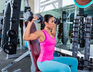 girl at gym seated dumbbell shoulder press