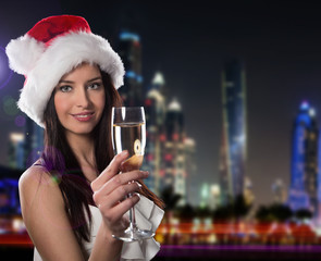 Young brunette woman with champagne glass in city at night. Cele