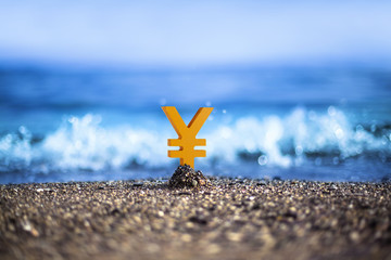 Japanese Yen currency icon is standing on the wavy sea side
