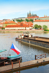 Prague castle and cathedral above Vltava river with Czech flag