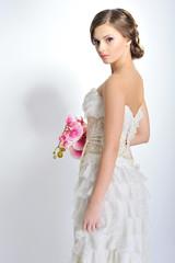 Slim beautiful woman with flowers wearing luxurious wedding dres