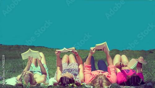 Leinwanddruck Bild friends reading under sunshine lying on the meadow