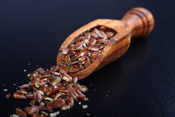 Broken flax seeds in wooden scoops on black background