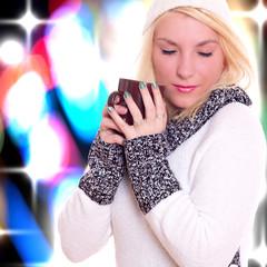 Junge blonde Frau hält Becher und genießt
