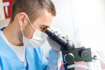 Close-up of man researcher using a microscope