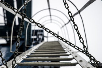 the way up a metal ladder blocked by a chain