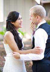 Handsome Caucasian groom talking with his biracial bride outdoor