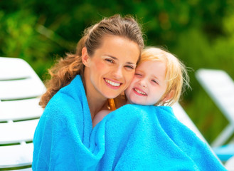 Portrait of smiling mother and baby girl wrapped in towel
