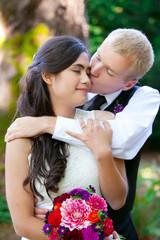 Caucasian groom lovingly kissing his biracial bride on cheek. Di