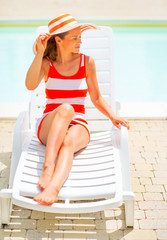 Young woman in hat sitting on sunbed and looking on copy space