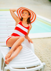 Young woman in hat relaxing on sunbed