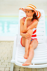 Portrait of thoughtful young woman in hat sitting on sunbed