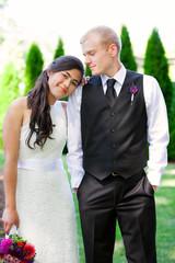 Caucasian groom holding his biracial bride, smiling. Diverse cou