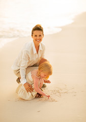 Happy mother and baby girl drawing on sand on beach