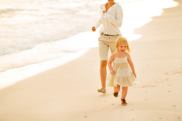 Mother and baby girl running on beach at the evening