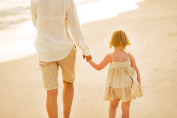 Closeup on mother and baby girl walking on beach at the evening