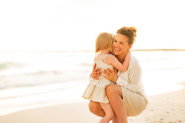 Happy mother and baby girl hugging on beach at the evening