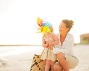 Smiling mother and baby girl behind colorful windmill toy