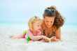 Happy mother and baby girl playing on beach