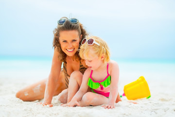 Smiling mother and baby girl playing on beach