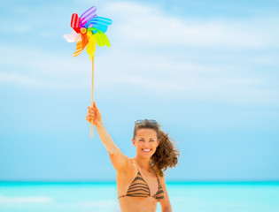 Smiling young woman showing colorful windmill toy on beach