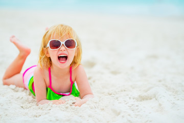Portrait of happy baby girl in sunglasses laying on beach
